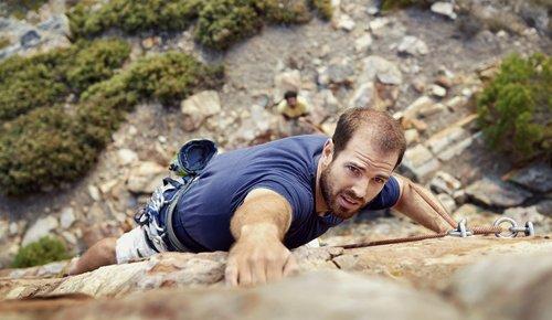 Ein Mann klettert eine Felswand hinauf