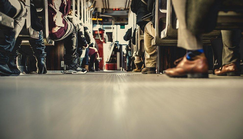 Menschen von hinten betrachtet, die im Zug sitzen.