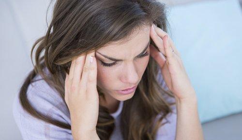 Eine Frau hält sich die Schläfen und verzieht schmerzhaft das Gesicht