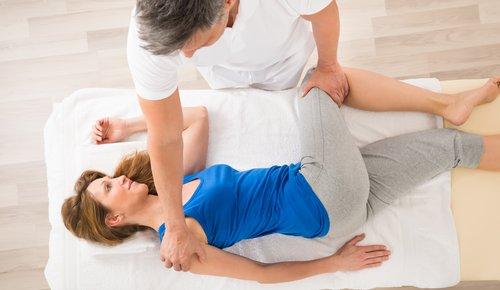 Durch gezielte Griffe behandelt der Shiatsu-Therapeut eine Patientin, welche auf der Seite liegt und ihren Körper verdreht