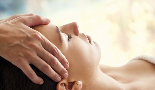 Mit sanften Druck legt ein Therapeut seine Hände auf den Kopf einer Patientin, welche entspannt liegt.