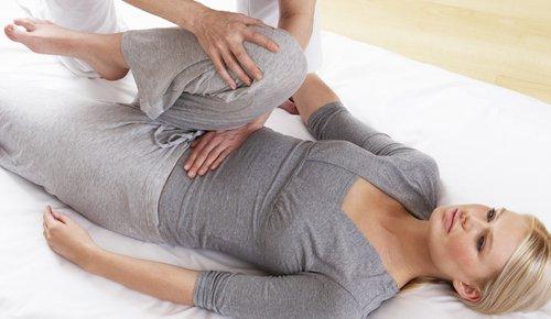 Eine junge Frau liegt und winkelt ihr Bein an. Der Therapeut berührt sie mit der einen Hand am Bauch, mit der anderen am Bein.