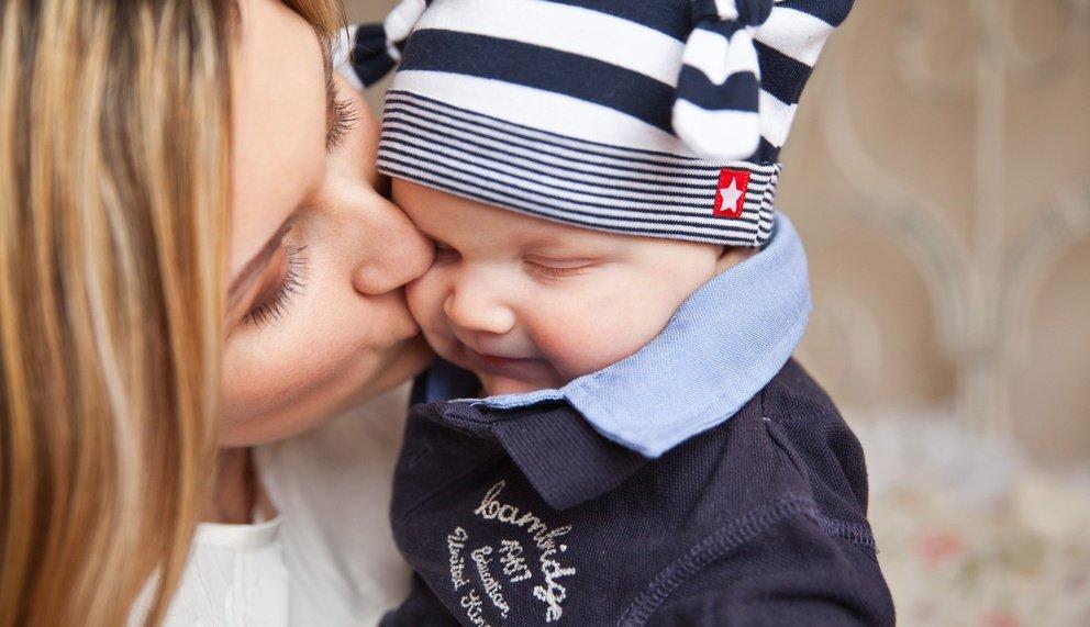 Eine gereifte Frau, die Ihr Kind küsst
