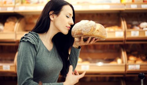 Eine Frau riecht genussvoll in einer Bäckerei an einem Laib Brot