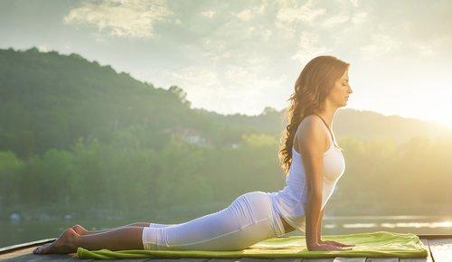 """Mit geschlossenen Augen betreibt eine junge Frau Yoga in der Natur und versucht sich an der Übung """"Kobra"""""""