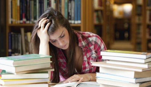 Studentin in Bibliothek lernt hinter Bücherstapel
