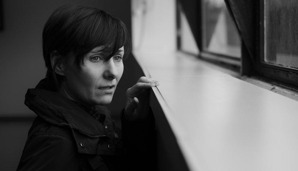 Eine traumatisierte Frau, die aus dem Fenster schaut