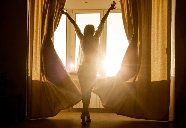 Frau begrüsst den Sonnenaufgang energievoll und mit Bewusstsein