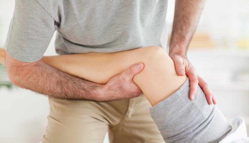 Shiatsu Therapeut löst Blockaden am Bein einer Patientin