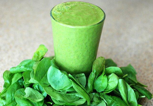 Ein Glas mit Grünem Smoothy, umrundet von grünen Blättern