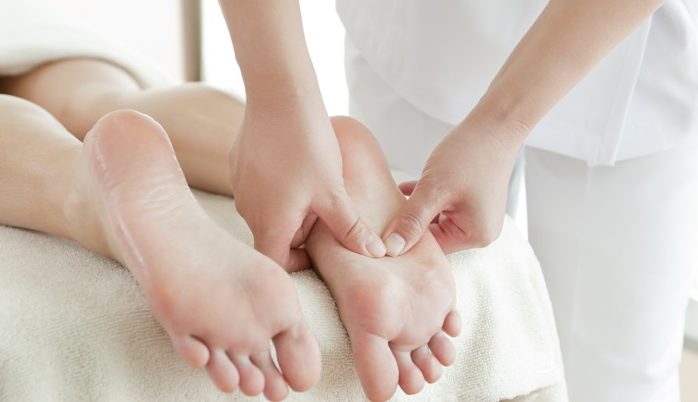 Therapeut behandelt Patienten mit Fussreflexzonenmassage