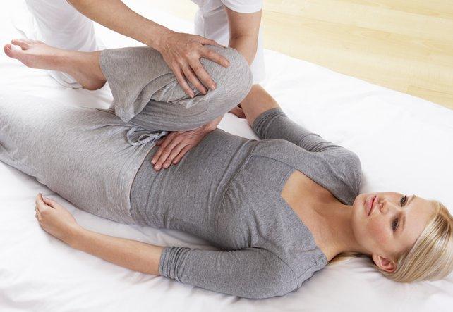 Eine junge Frau liegt und winkelt ihr Bein an. Der Therapeut berührt sie mit der einen Hand am Bauch beim Shiatsu