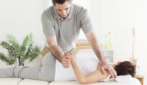 Eine Frau liegt und lässt sich mit den Händen eines Therapeuten am Hald berühren