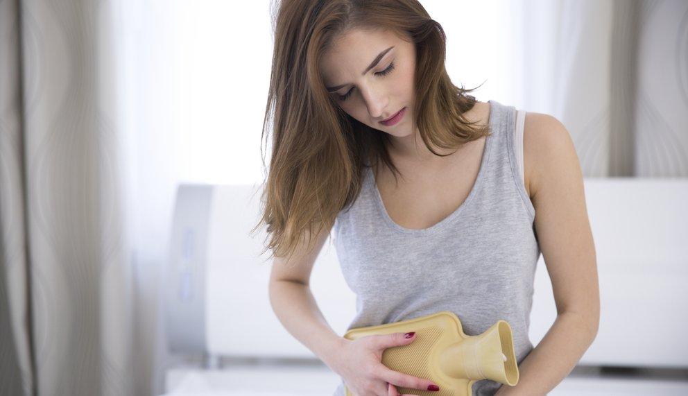 Eine junge Frau wirkt vom Gesichtsausdruck so als hätte sie Schmerzen und hält sich eine gelbe Wärmflasche an den Bauch