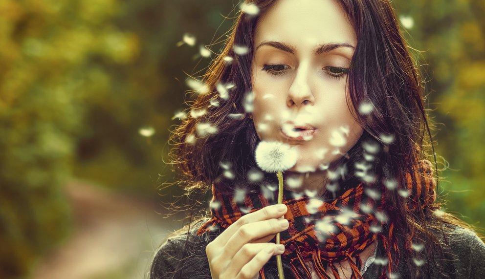 Frau ohne Heuschnupfen pustet Löwenzahn-Blüten