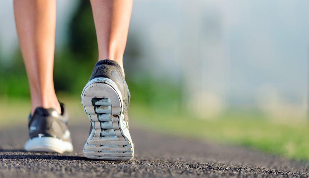 Zu sehen sind die Füsse eines Läufers auf Asphalt