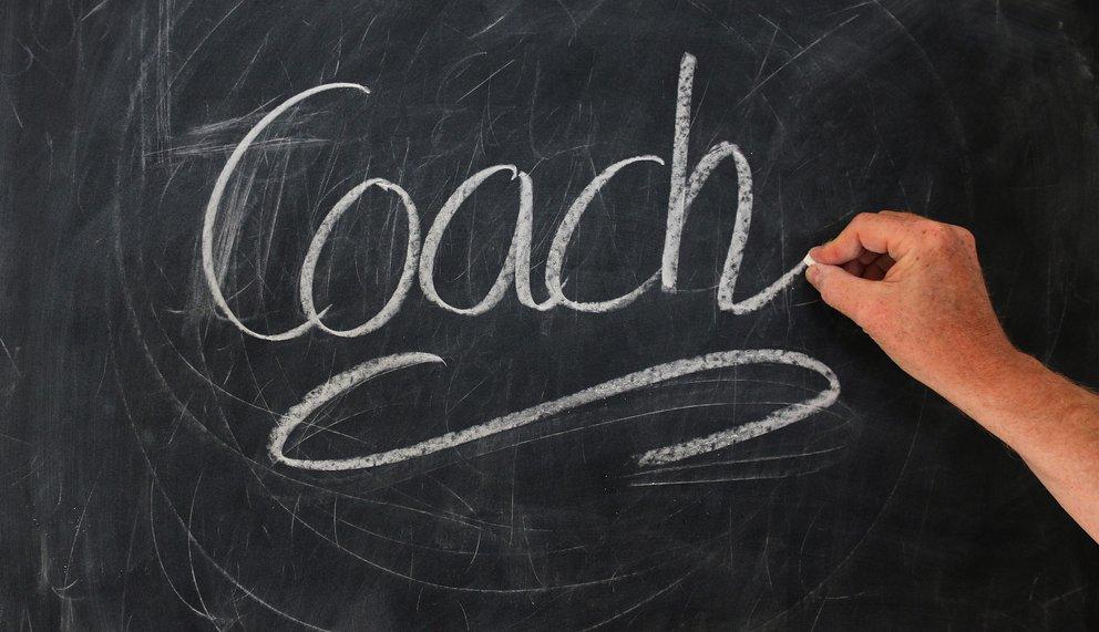 Eine Hand hat gerade das Wort Coach geschrieben