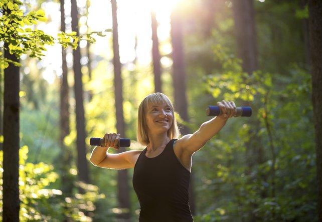 Ehemalige Burnout Patientin mit Gewichten im Wald