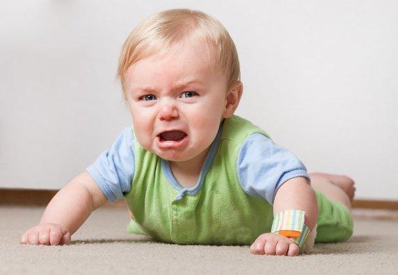 Ein schreiendes Baby liegt auf dem Bauch und schaut in die Kamera