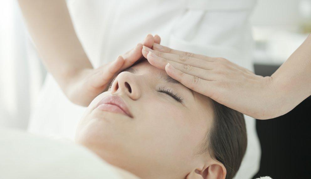 Eine Frau liegt mit geschlossenen Augen und ein Therapeut legt behutsam seine Hände auf ihre Stirn