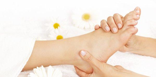 Behutsam wird ein Fuss mit den Händen massiert. Im Hintergrund befinden sich weiss, gelbe Blüten.