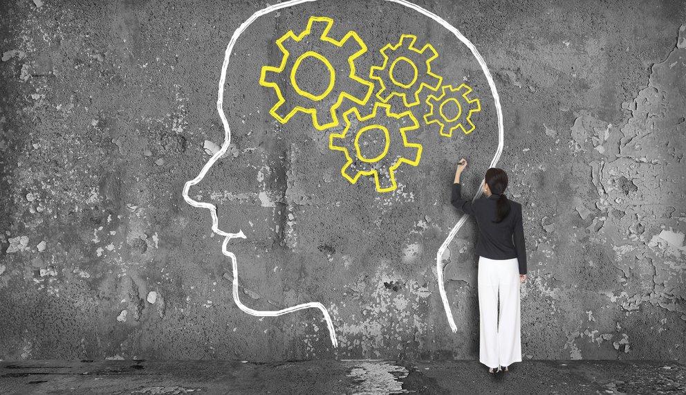 Frau zeichnet Kopf mit Zahnrädern als Gehirnmasse