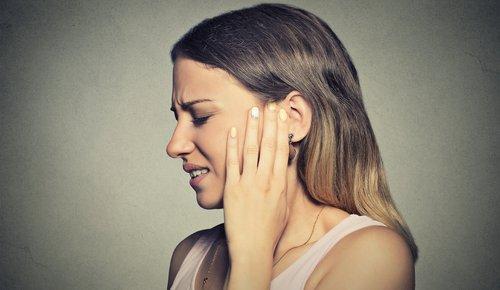 Frau fasst sich schmerzvoll an den Hals wegen Stillen Reflux