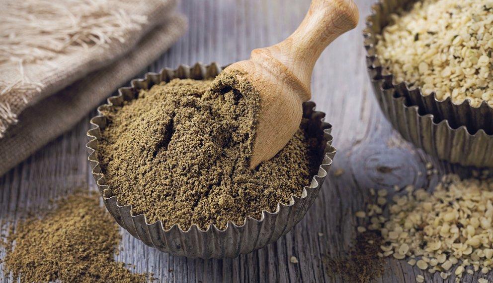 Gelblich, braunes Pulver und helle Samen liegen verteilt in und neben Schalen aus Metall. Dahinter befindet sich Leinenstoff.
